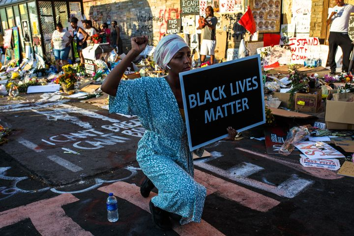 A Somali American protester kneels during a call for justice for George Floyd outside the Cup Foods store, where Floyd was ki