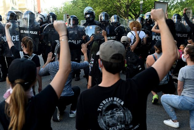 Protesters kneel and hold up their hands in front of a row of police during a demonstration against police...