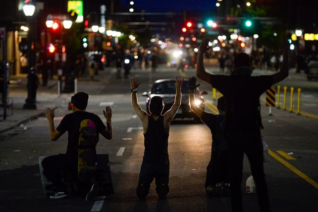 Protesters kneel on May 31 during the fourth consecutive day of protests in Denver following the death...