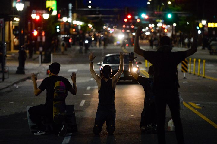 Protesters kneel on May 31 during the fourth consecutive day of protests in Denver following the death of George Floyd.