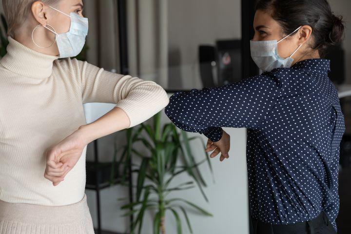 Συνάδερφοι στο γραφείο φορούν μάσκες και χαιρετιούνται με τον ώμο, καθώς διατηρούν τις απαραίτητες αποστάσεις.