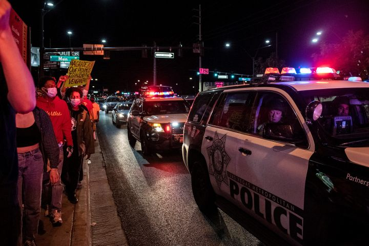 Police officers look outside their car window as people march in a Black Lives Matter rally in downtown Las Vegas on June 1.