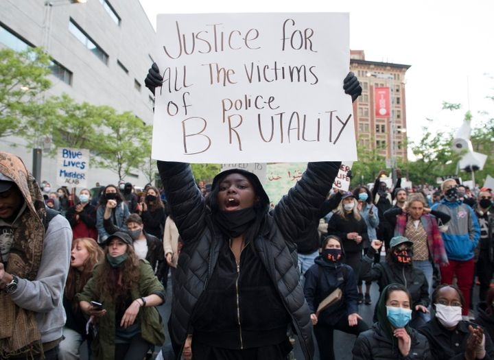 A anti-police brutality protester hold a sign during a demonstration calling for justice in the death of George Floyd and victims of police brutality in Montreal on  May 31, 2020.