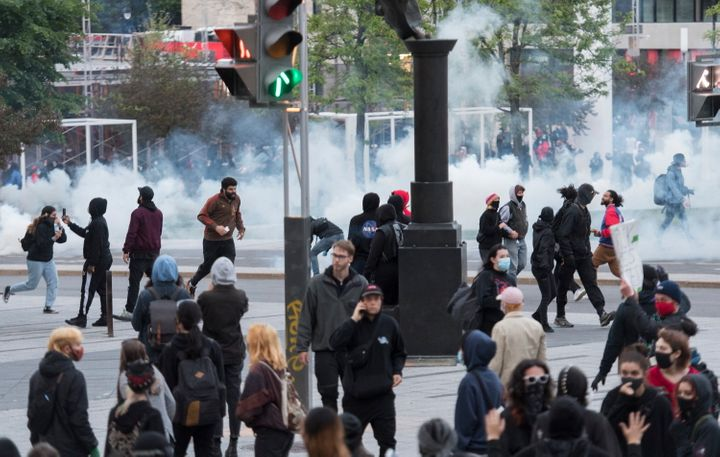 Protesters run from police during a demonstration calling for justice in the death of George Floyd and victims of police brutality in Montreal on May 31, 2020.