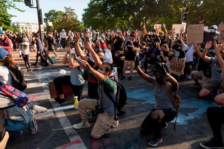 Protestors take a knee and raise their hands as they face riot police near the White House on June 1 as demonstrations agains