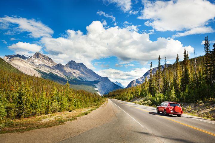 A car drives through Banff National Park in Alberta.