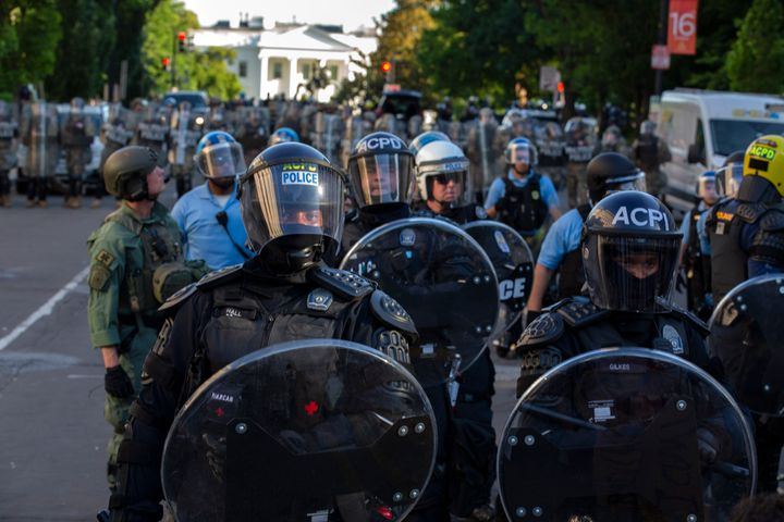 The White House looms in the background behind a line of law enforcement officers wearing riot gear as they push back demonst