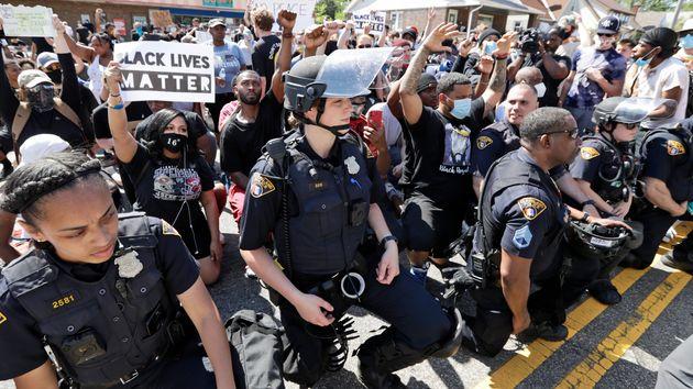 Les policiers et les manifestants se mettent à genoux ensembleà Cleveland, lors d'un...