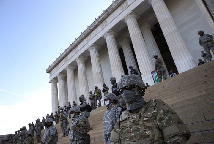 Members of the D.C. National Guard stand on the steps of the Lincoln Memorial as demonstrators participate in a peaceful prot
