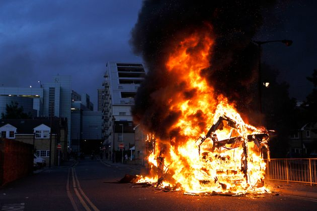 A bus is set on fire as rioters gathered in Croydon, south London, on August 8