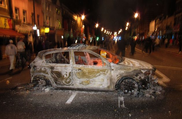 People gather near the remains of a police patrol car left after being set on fire during a protest in