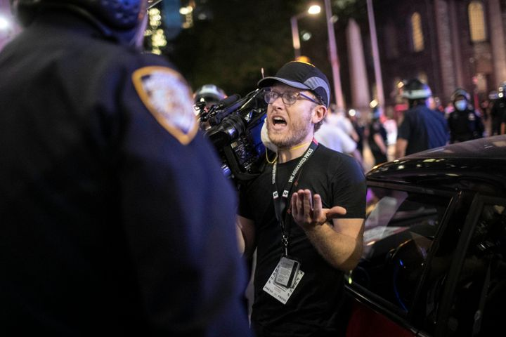 "Associated Press videojournalist Robert Bumsted reminds a police officer that the press are considered ""essential worke"