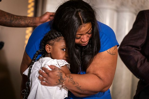 George Floyd's daughter Gianna Floyd, 6, gives her mother Roxie Washington a hug during a press conference...