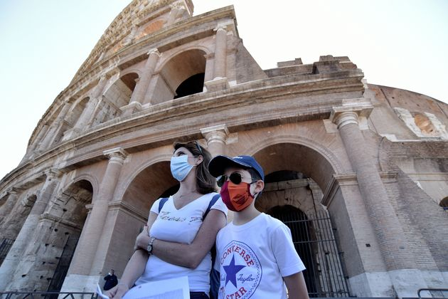People wearing face masks visit the Colosseum on June 1, 2020, in Rome, after three months of closure...
