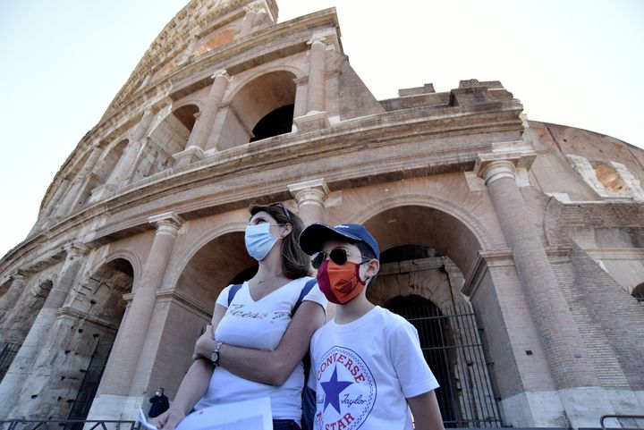 People wearing face masks visit the Colosseum on June 1, 2020, in Rome, after three months of closure due to coronavirus lock