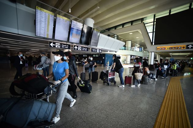 Travelers walk across a terminal at Rome's Fiumicino airport on June 3, 2020, as airports and borders...