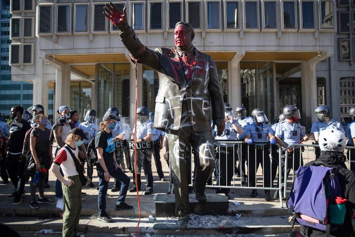 Police stand near the former mayor's vandalized statue on May 30 during protests over the death of George Floyd.
