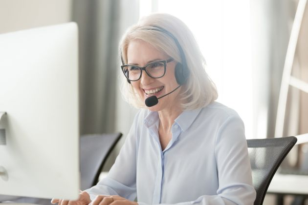Happy old businesswoman in headset speaking by conference call looking at computer, mature female aged...