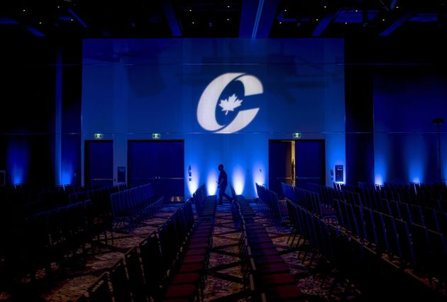 A man is silhouetted walking past a Conservative Party logo before the opening of the Party's national...