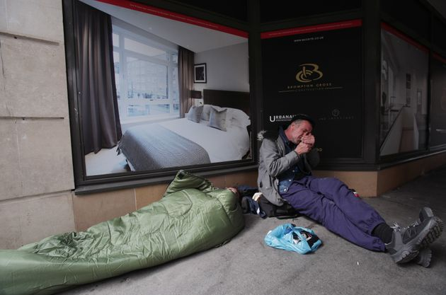 People sleeping rough next to a display advertising luxury apartments, in Victoria,