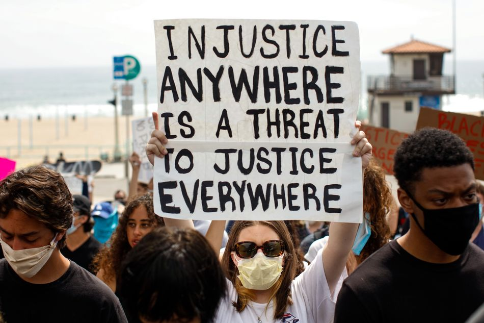 """A woman holds up a sign with the Martin Luther King Jr. quote """"Injustice anywhere is a threat to justice everywhere"""" during a protest inManhattan Beach, California, on June 2."""