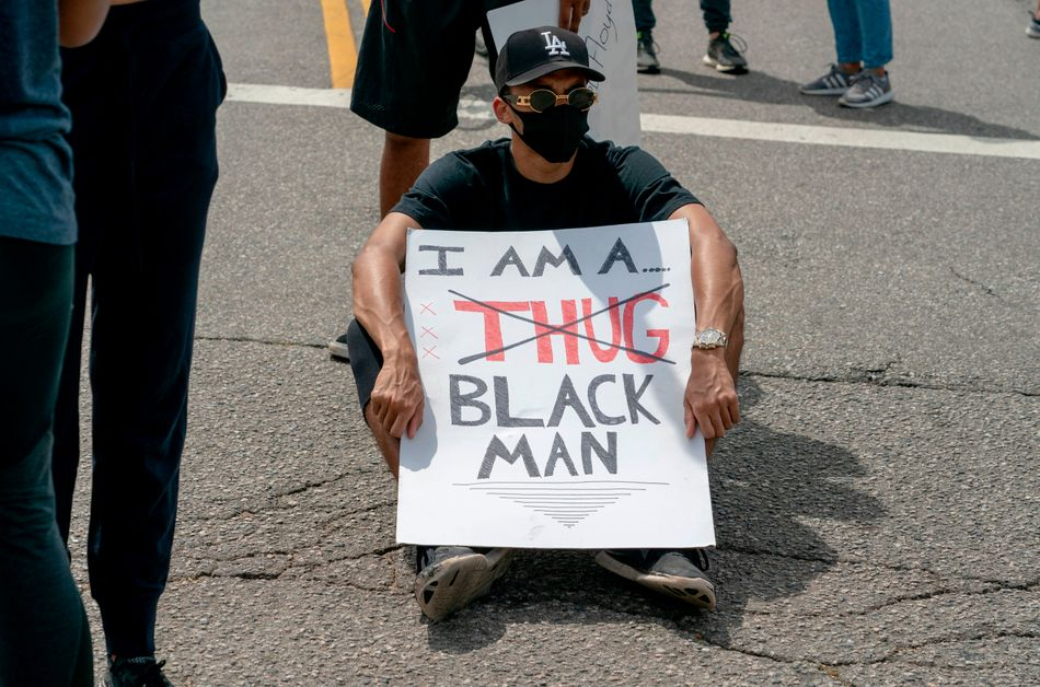 A seated protester holds a signduring a June 2 demonstration in Los Angeles over the death of George Floyd.
