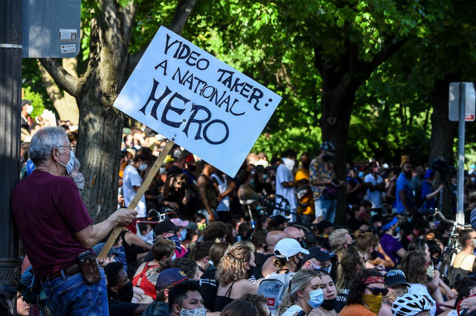 """Protesters gather outside the residence of Minnesota Gov. Tim Walz on June 1. One man's sign reads: """"Video taker: A national hero."""""""