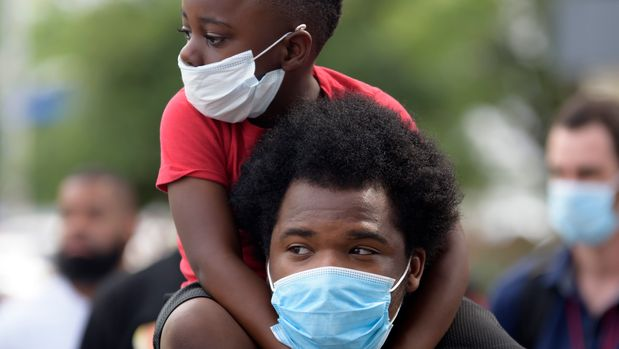 "A young boy sits on the shoulder's of a man, both wearing facemasks, during a ""Justice for George Floyd"" event in Houston, Texas on May 30, 2020, after George Floyd, an unarmed black, died while being arrested and pinned to the ground by a Minneapolis police officer. - Clashes broke out and major cities imposed curfews as America began another night of unrest Saturday with angry demonstrators ignoring warnings from President Donald Trump that his government would stop violent protests over police brutality ""cold."" (Photo by Mark Felix / AFP) (Photo by MARK FELIX/AFP via Getty Images)"