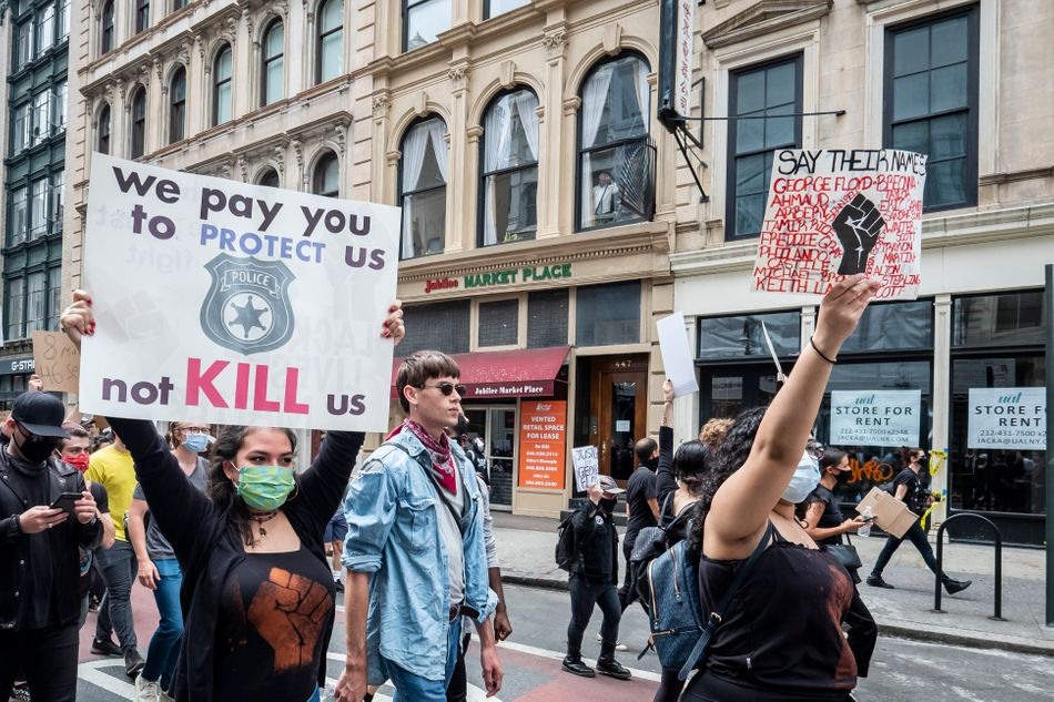 """New York City demonstrators walk from Foley Square past 1 Police Plaza on their way to Washington Square Park for a peaceful moment of reflection for those killed by police. The sign on the left reads: """"We pay you to protect us, not kill us."""""""