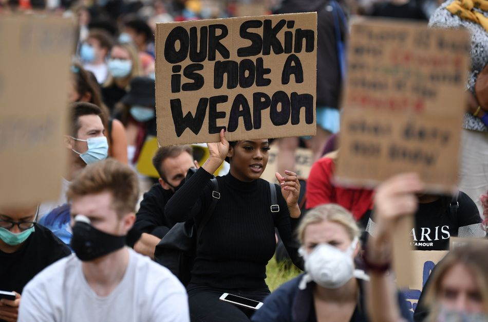 """A protester at an anti-racism demonstration in London on June 3 holds a sign that reads: """"Our skin is not a weapon."""""""