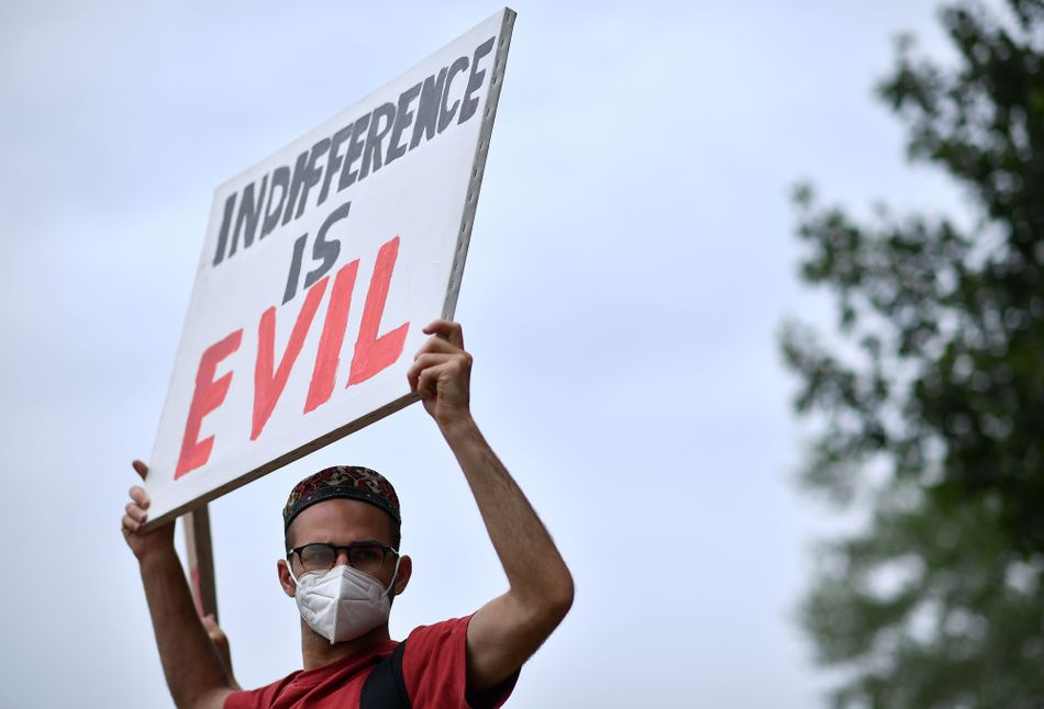 """Protester holds a sign that says """"Indifference is evil"""" during an anti-racism demonstration in London on June 3."""