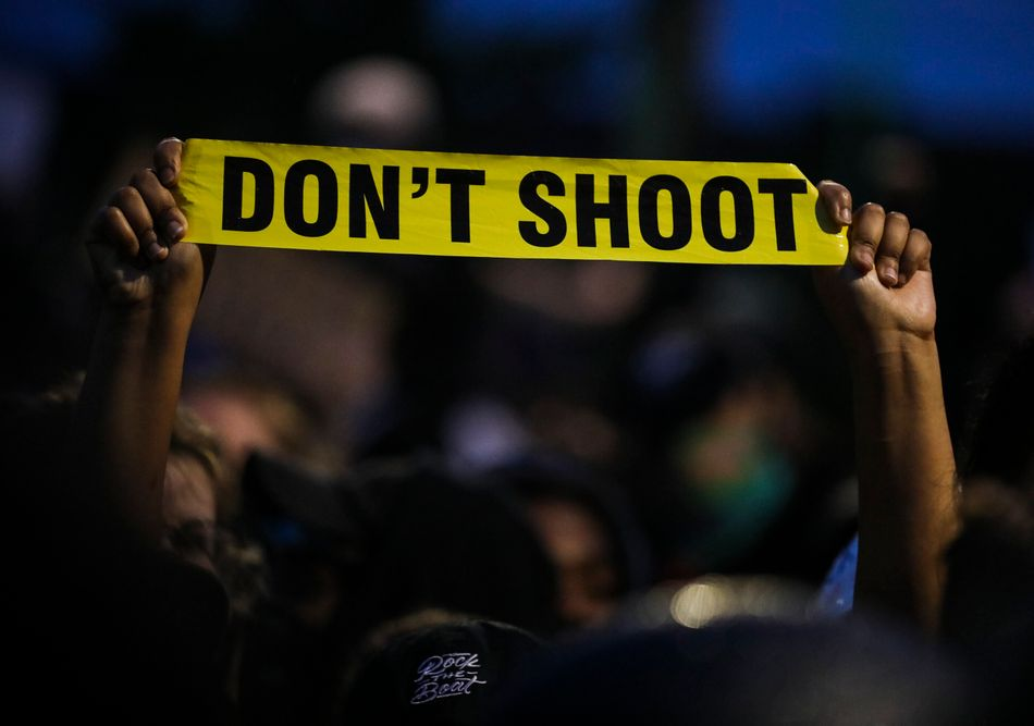 """A protester holds up a piece of yellow plastic that reads, """"Don't shoot"""" while participating in a demonstration outside the Forest Hills MBTA Station in Boston on June 2."""