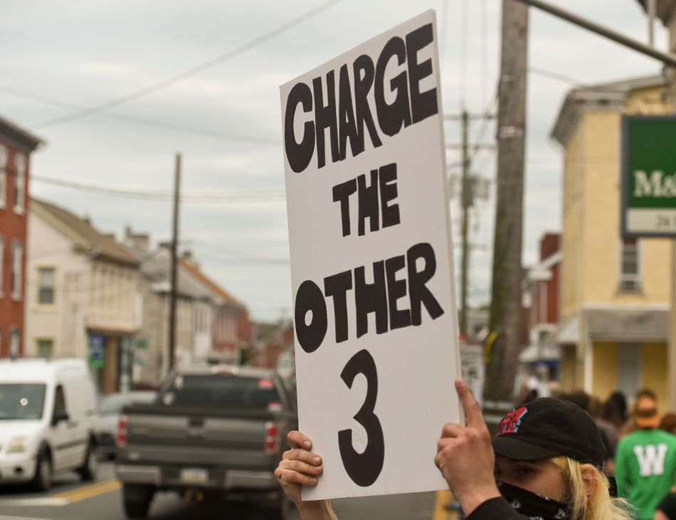 """In Boyertown, Pennsylvania, a protester holds a sign that says """"Charge the other 3,"""" referring to the other three police officers present when their colleague kneeled on George Floyd's neck and killed him. The former officers have since been charged with aiding and abetting."""