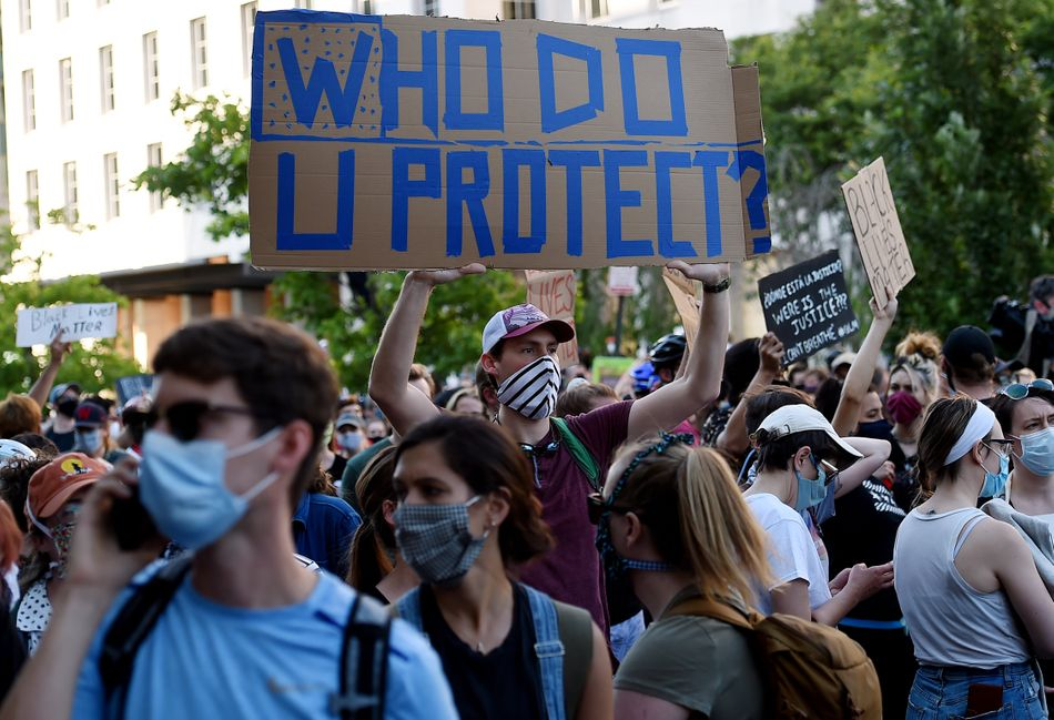 """Demonstrators protesting the death of George Floyd hold up placards near Lafayette Park across from the White House on June 2 in Washington, D.C. The sign in the center reads: """"Who do u protect?"""""""
