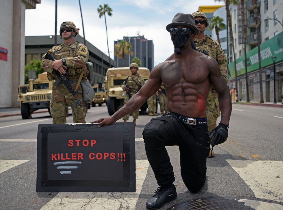 """A protester kneels as he holds a placard that says """"Stop killer cops!!!!"""" in front of a row of Army National Guard troops during a June 2 demonstration in Hollywood, California."""