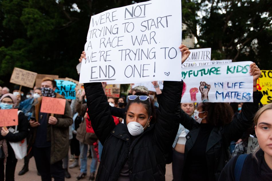 """In Sydney, protesters prepare to march on Parliament House at the Archibald Fountain in Hyde Park on June 2. The one in the foreground reads: """"We're not trying to start a race war. We're trying to end one."""""""