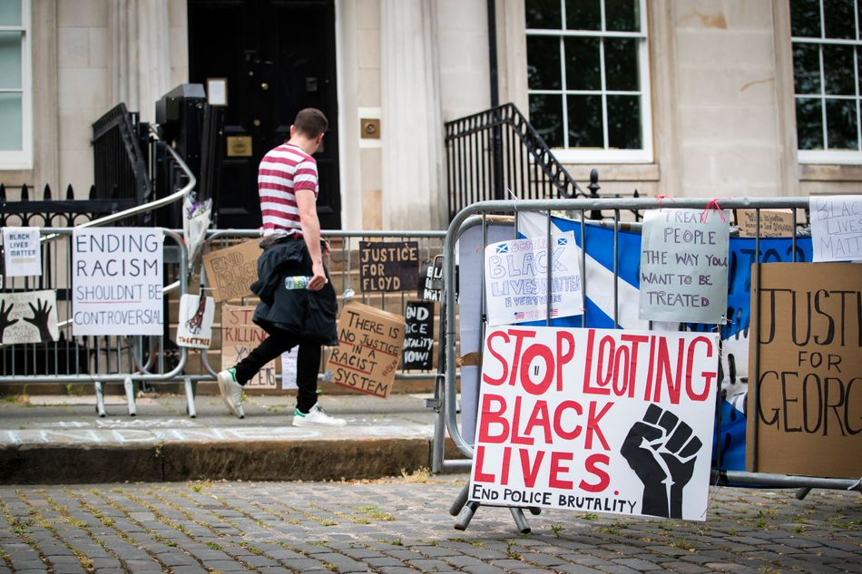 """Protest signs posted outside the U.S. Consulate General in Edinburgh, Scotland, in response to the police killing of George Floyd. One reads: """"Stop looting Black lives. End police brutality."""""""
