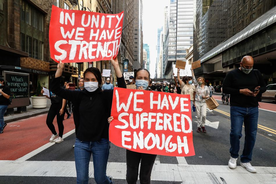 """New York protesters take part in a June 1 demonstration in response to the death of George Floyd. The sign on the left reads: """"In unity we have strength;"""" the one on the right reads: """"We have suffered enough."""""""