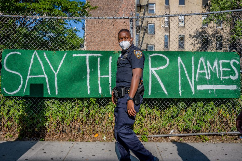 """An NYPD officer walks by a banner reading """"Say Their Names"""" on June 1 in Brooklyn, New York."""