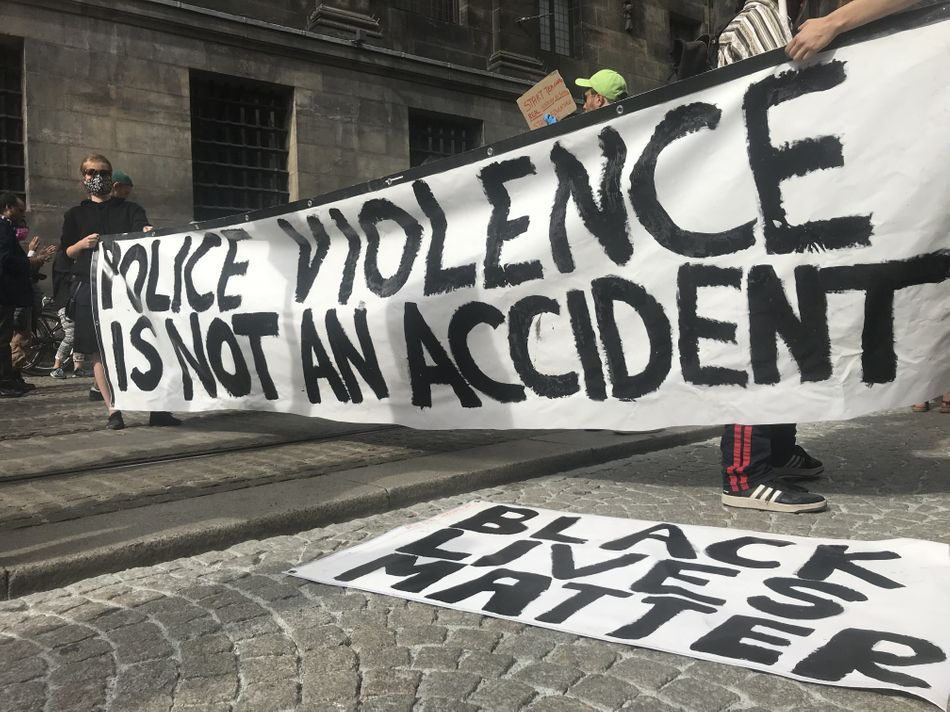 """People shout slogans during a June 1 protest at Dam Square in Amsterdam over the death of George Floyd. The banner reads: """"Police violence is not an accident."""""""