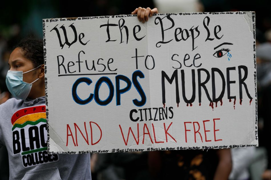 """People carry a banner that says """"We the people refuse to see cops murder citizens and walk free"""" as they march to protest the death of George Floydon May 31 in Portland, Oregon."""