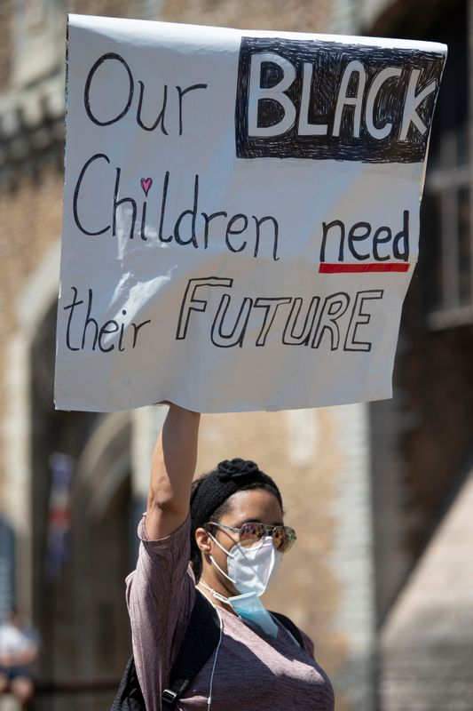 """A woman holds up a sign that says """"Our black children need a future"""" during a May 31 protest outside Cardiff Castle in Wales/"""