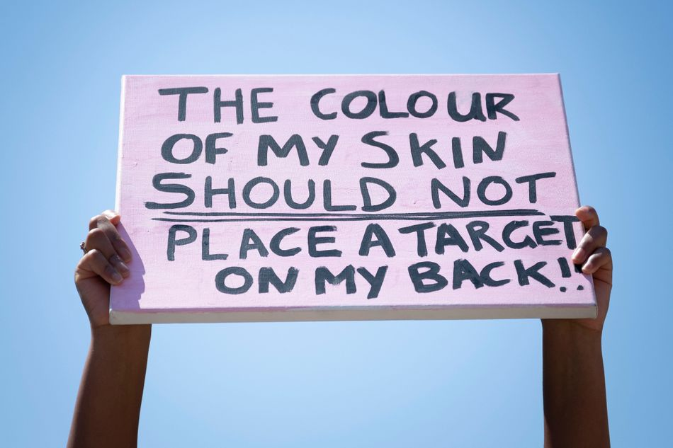 """A close-up of a sign that says: """"The colour of my skin should not place a target on my back"""" during a May 31 protest outside Cardiff Castle in Wales."""