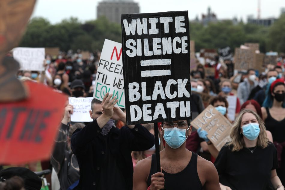 """During a Black Lives Matter protest in London's Hyde Park on June 3, aprotester holds up a sign that says """"White silence = Black death."""""""