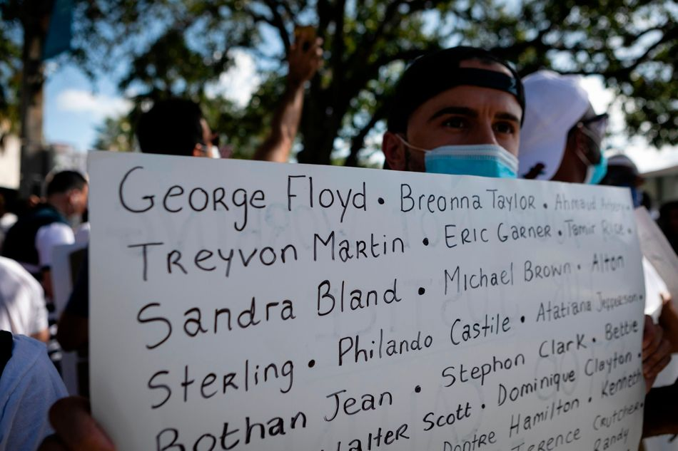 A protester holds a sign with the names of victims of police brutality during a rally in Coral Gables, Florida, on May 30.