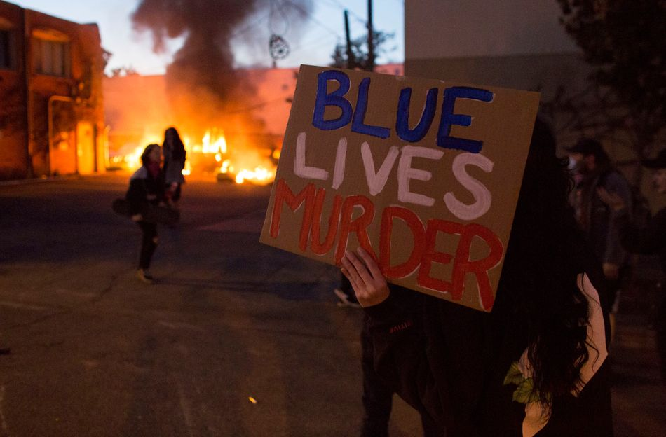 """A protester holds a sign that says """"Blue Lives Murder"""" on May 29 in Minneapolis."""