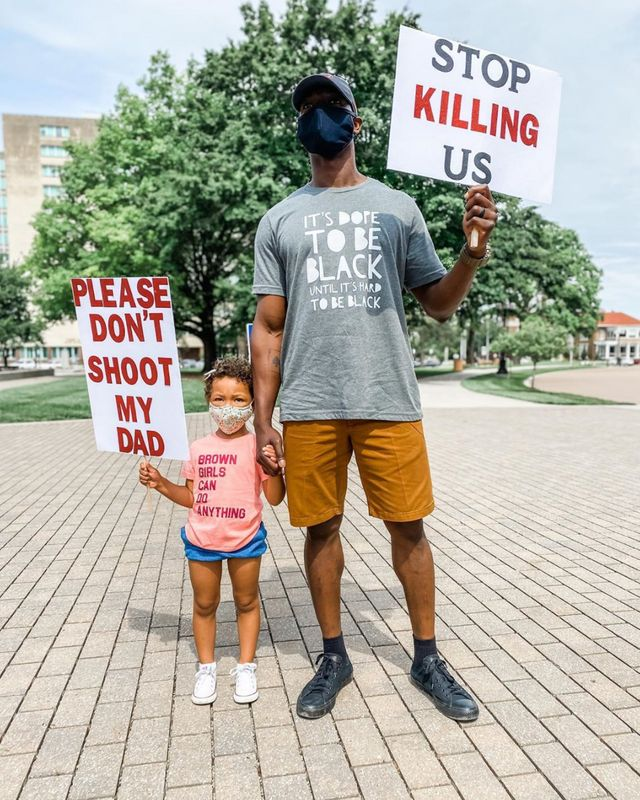 """Breezy Rose of Kansas posted this photo of her husband holding a sign that says """"Stop killing us"""" and her daughter holding a sign that says """"Please don't shoot my dad"""" on Instagram. In the caption, Breezy wrote: """"When I tell you I cried after snapping this picture at a rally for George Floyd today, I sobbed. This is our reality. This is reality for every black person in our country. Today I wept for George Floyd, for Breonna Taylor, for Ahmaud Arbery, for Eric Garner, for Sandra Bland, for Tamir Rice and for so many others. Today I wept for my husband having to teach this to our daughter. And today I wept for our daughter, who has to grow up with this fear. Today, we wept. But tomorrow, we fight."""""""