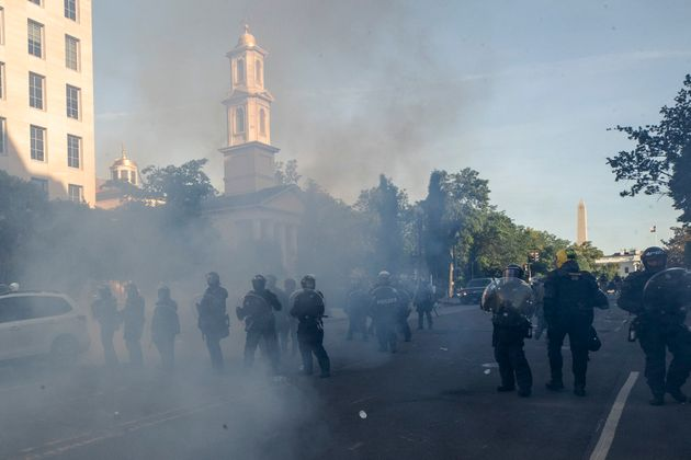 Tear gas floats in the air as a line of police moves demonstrators away from St. John's Church on