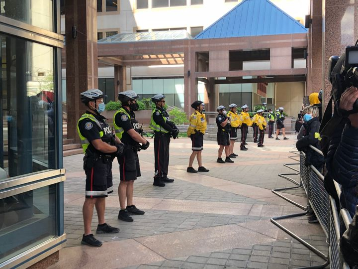 Toronto police line barricade their headquarters in downtown Toronto during protests over the death of Regis Korchinski-Paquet on May 30, 2020.