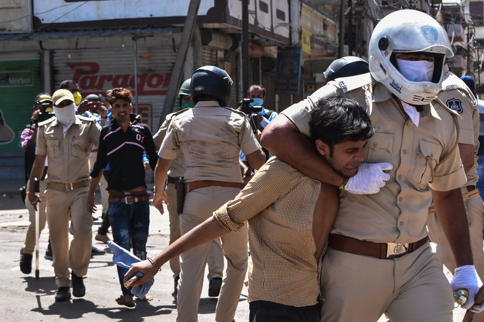 Gujarat Police personnel detain stranded migrant workers during a protest in Surat on May 4. Protesting...